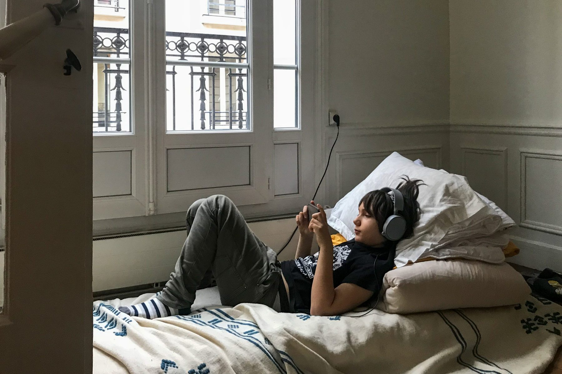 young boy laying in bedroom using smartphone device