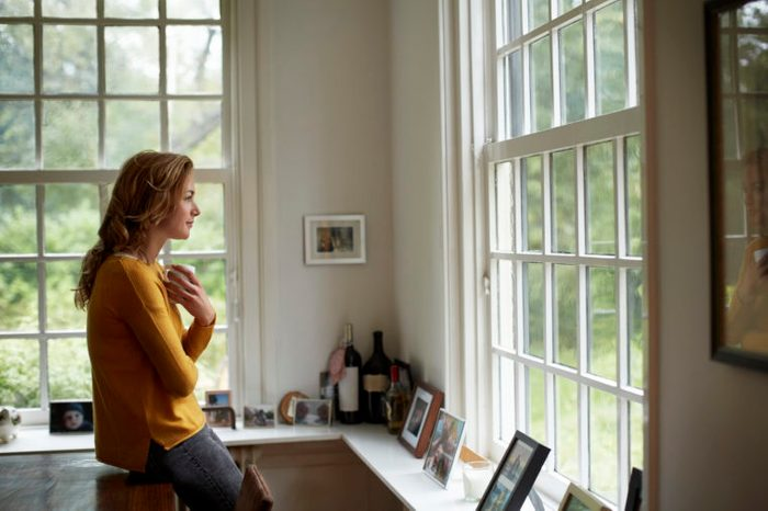 woman in home kitchen looking out window