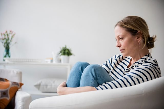 woman sitting in chair at home thinking