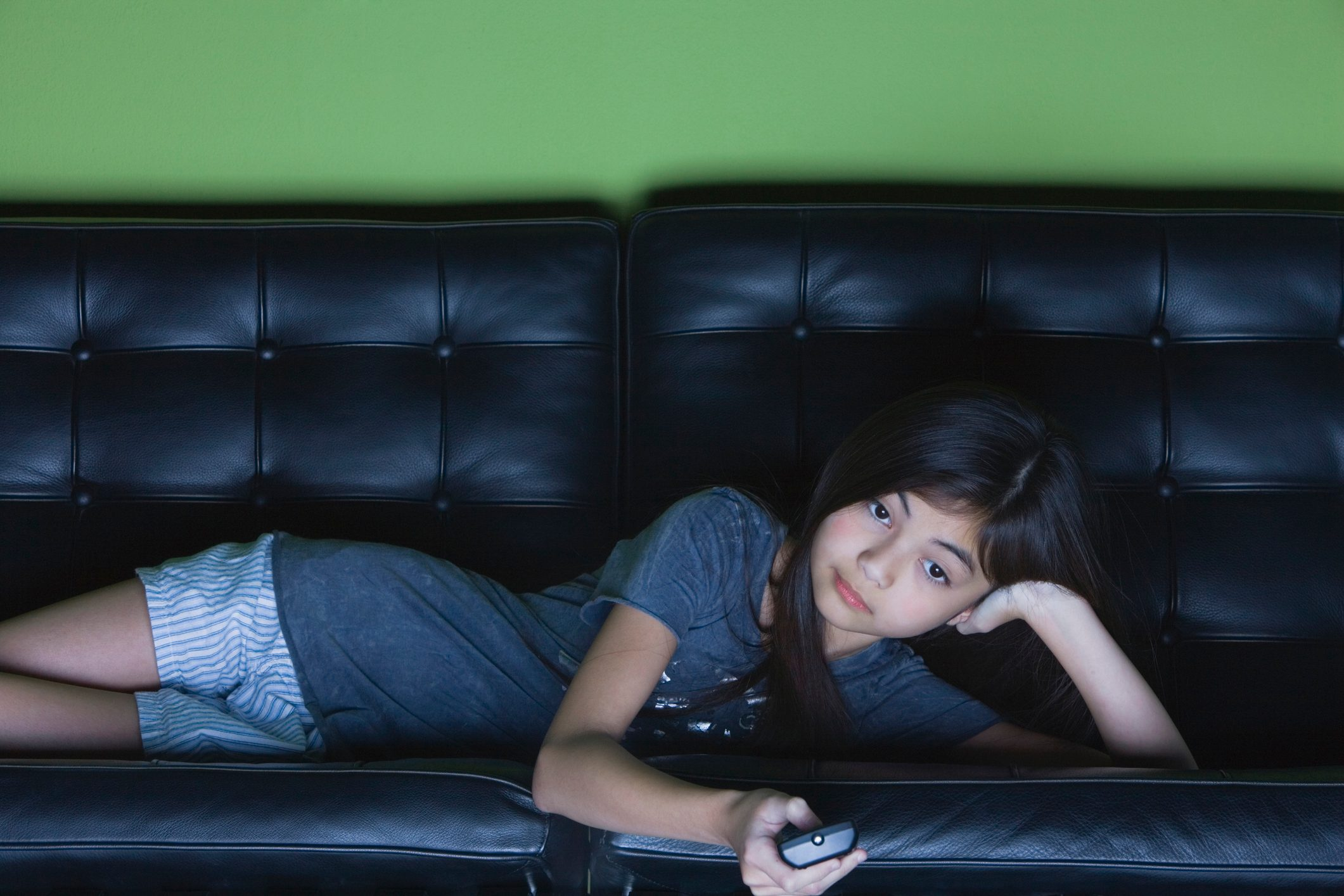 young girl lying on couch watching television