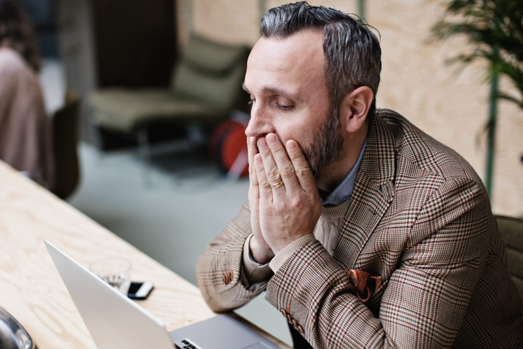 upset businessman looking at laptop