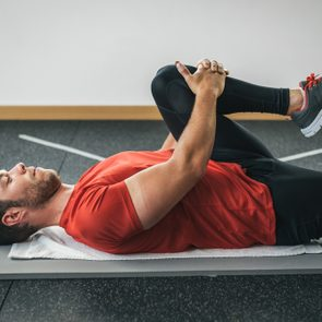 healthy man stretching leg before gym workout. Fitness strong male athlete. Male young fit exercising.