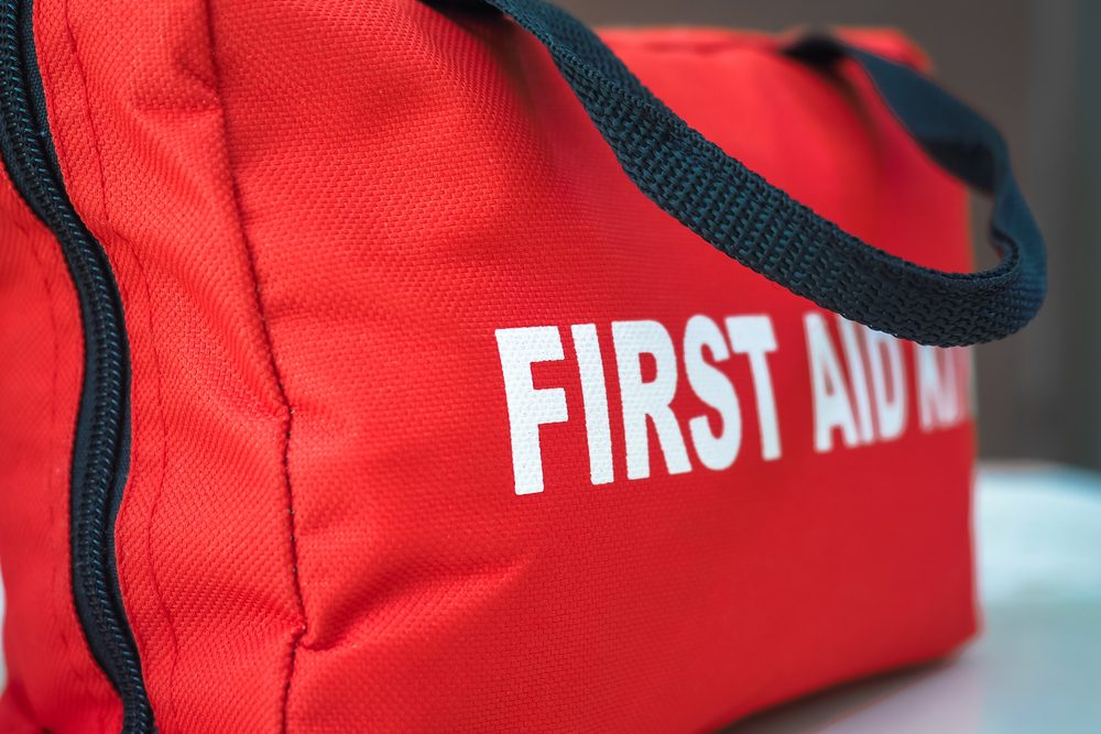 First Aid KitA red first aid kit bag with a black zip and handle, in closeup.