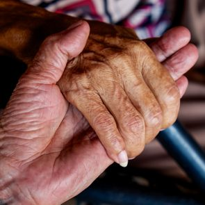 The old man's hand touching the hand of a sick old woman