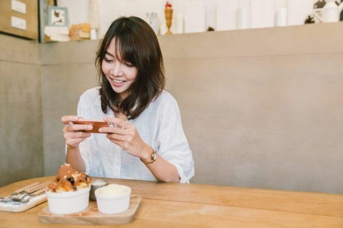 Beautiful Asian girl taking photo of chocolate toast cake, ice-cream, and milk at coffee shop.