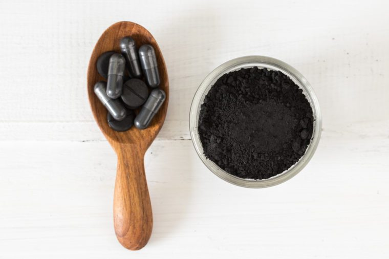 Activated charcoal powder in a glass bowl and pills on a spoon on white table