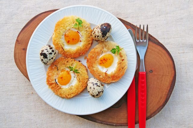 Small white plate topped with poached egg in a basket and quail eggs.