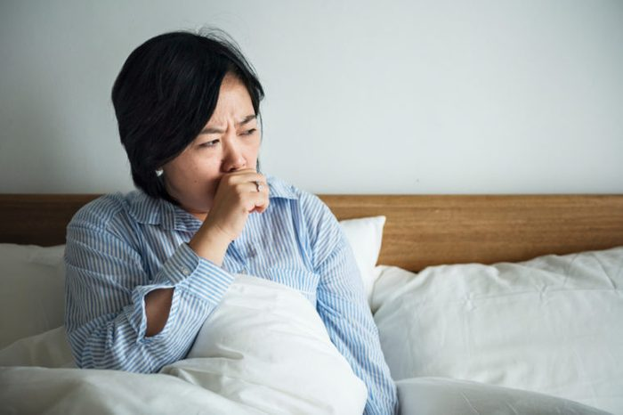 A woman coughing in bed