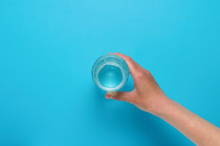 Female hand taking a glass of water.