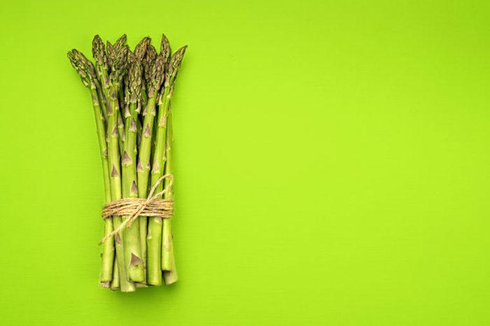 A bunch of fresh green asparagus on green background.
