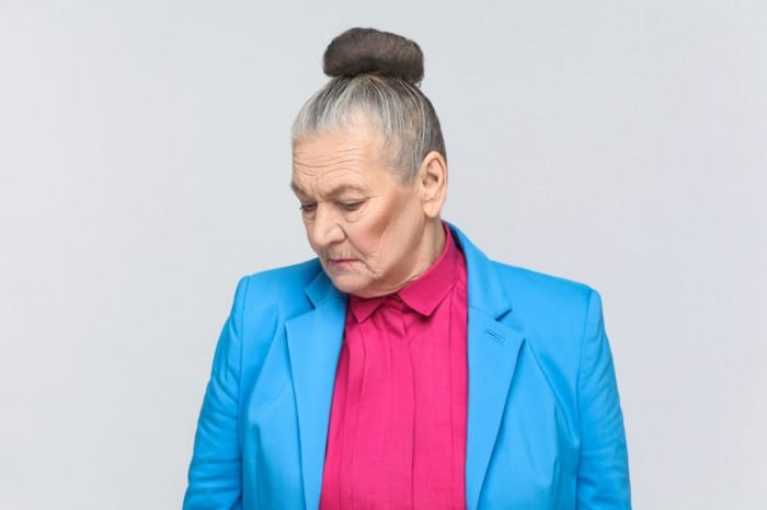 Gray haired woman in bright clothing looking down.
