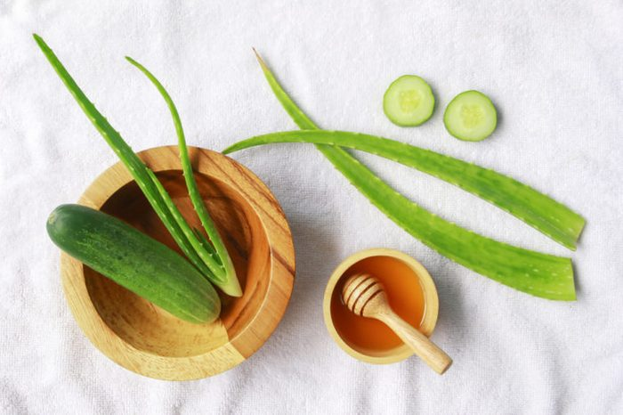 Aloe vera and cucumber with honey on white fabric background