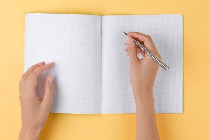 Woman writing in a notebook.