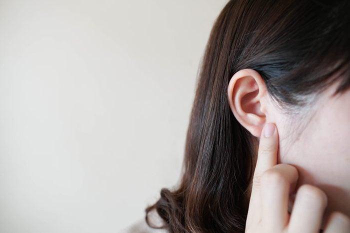 woman touching ear ache