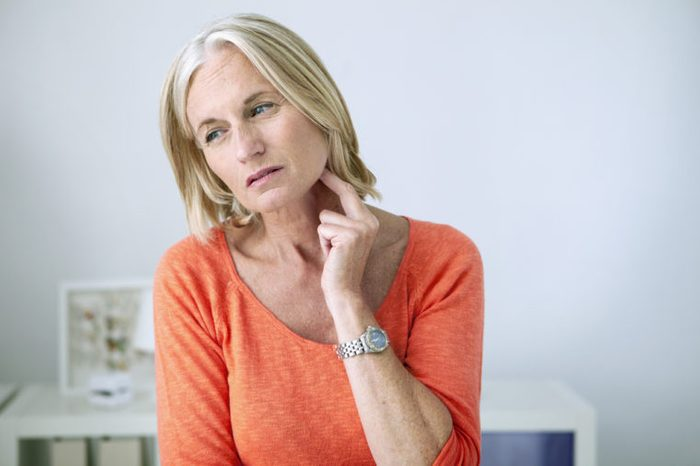 woman touching lymph nodes in neck