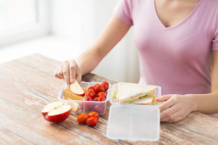 Woman with lunch packed in containers with divided sections.