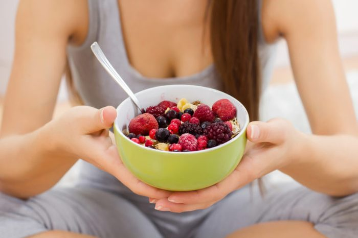 Young woman holding a bowl of granola topped with berries..