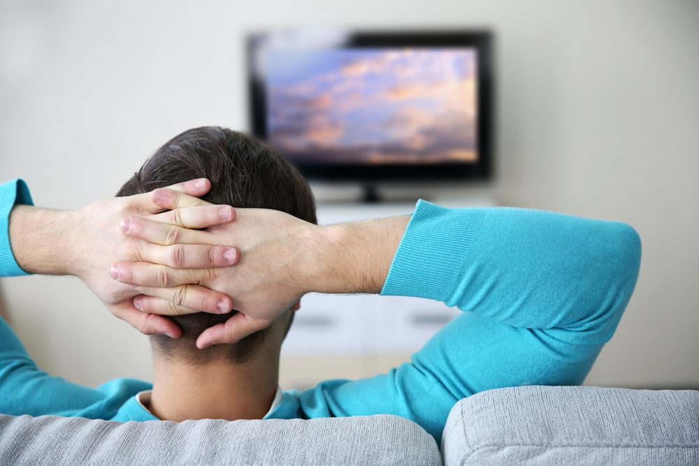 man watching TV on a sofa at home