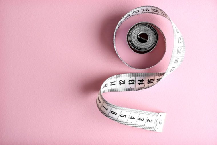 A measuring tape on a pink background.