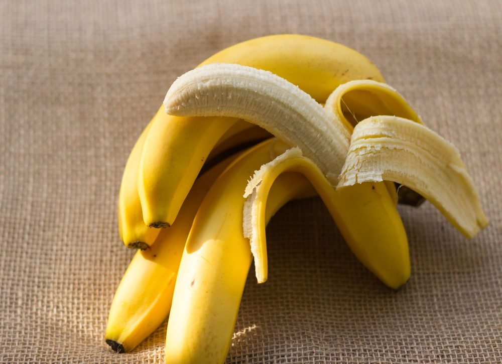 bunch of bananas and one peeled banana