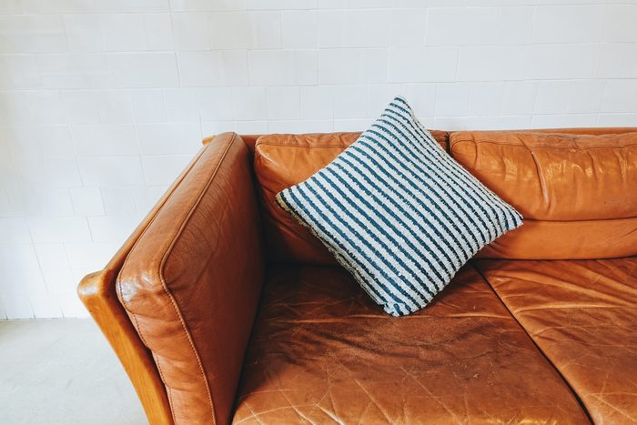Vintage brown leather couch with pillow in living room