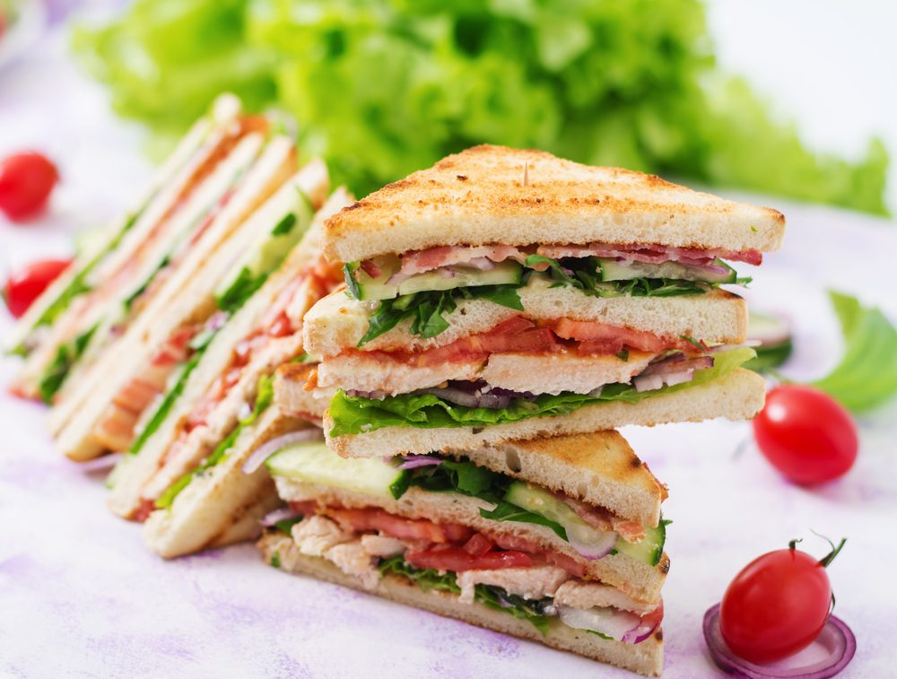 Club sandwich with chicken breast, bacon, tomato, cucumber and herbs.