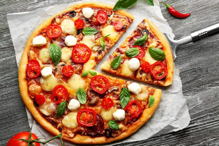 Fresh pizza with tomatoes, cheese and mushrooms on wooden table closeup
