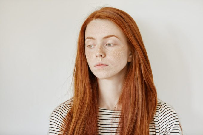 Indoor portrait of sad young woman wearing her long ginger hair loose looking down with unhappy face expression after breaking up with her boyfriend. Upset teenage girl with freckles feeling blue