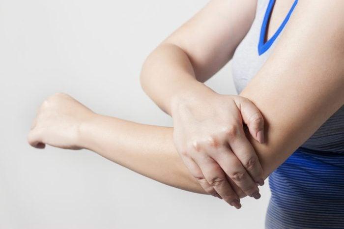 Woman holding arthritic elbow