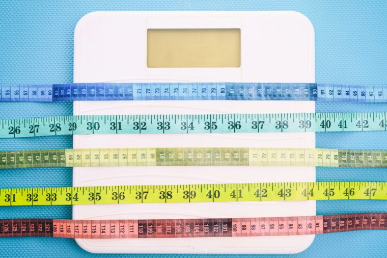 Bathroom scale and measure tapes on a blue background.