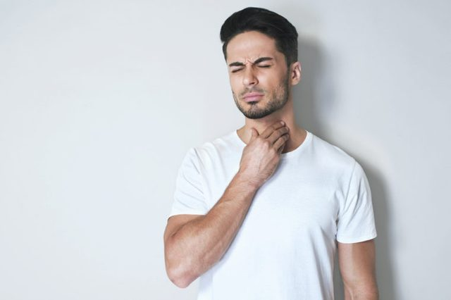 Man with sore throat touching his neck