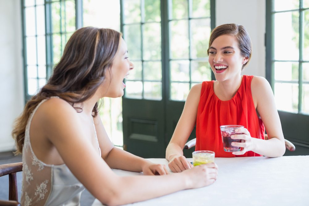 Friends laughing while having cocktails