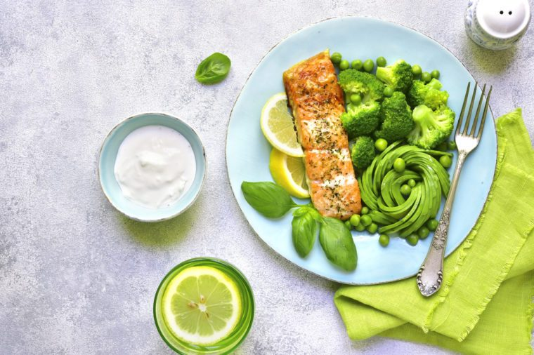 Grilled salmon garnished with green vegetables on a blue plate.