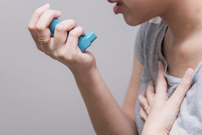 Woman using a pressurized cartridge inhaler