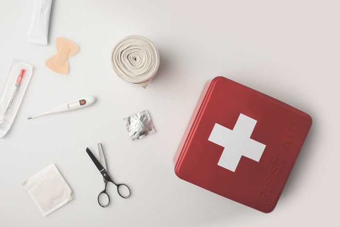 Top view first-aid kit with medical supplies isolated on white