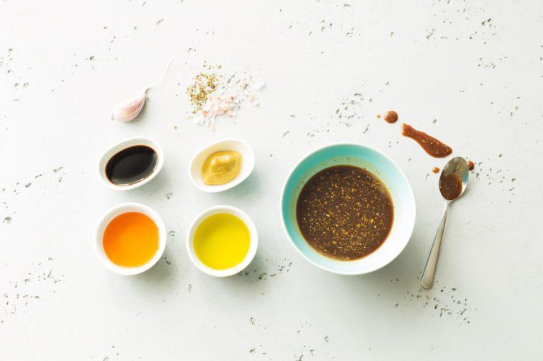 Homemade salad dressing and ingredients, including balsamic vinegar, honey, olive oil, mustard, garlic, and salt.
