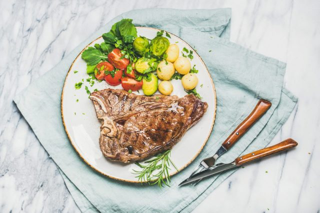 Grilled steak with vegetables and fresh rosemary on a plate.