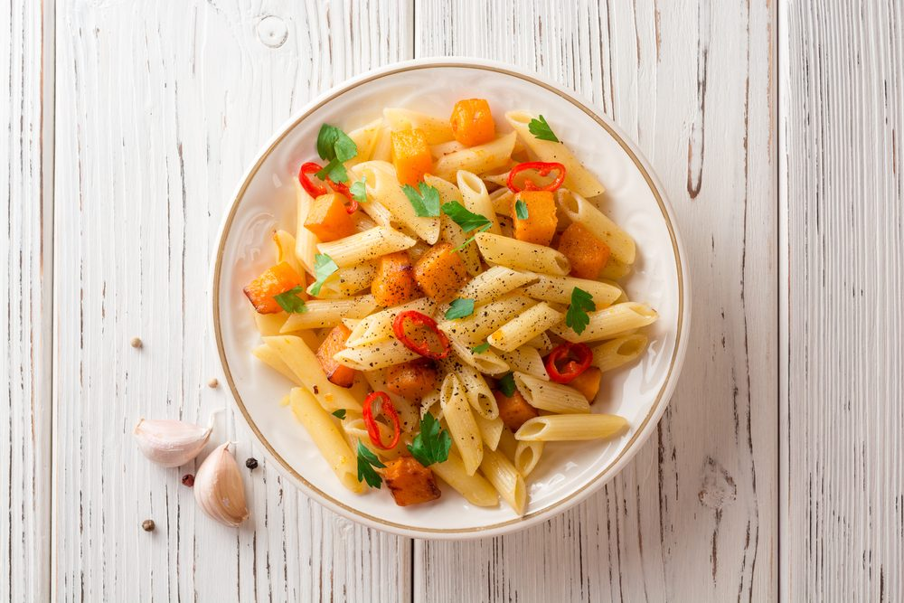 Penne pasta with pumpkin, chilli and parsley in plate on white wooden background. Top view.