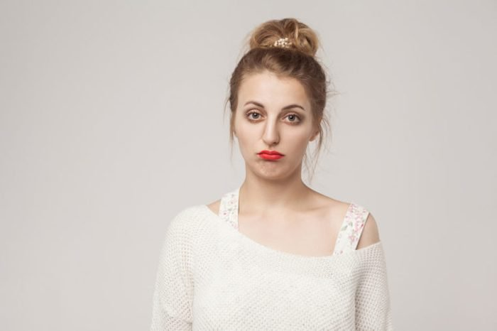 Young lady puffs her lips in sad expression.