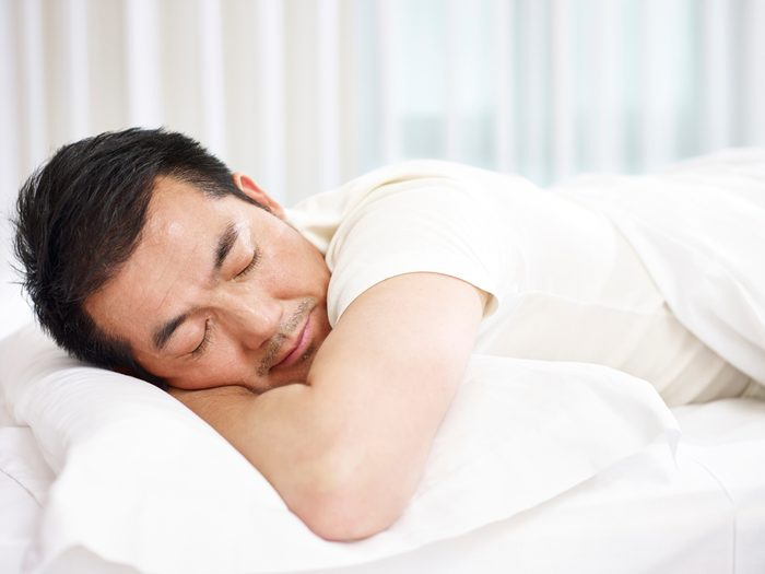 man lying on front in bed sleeping.