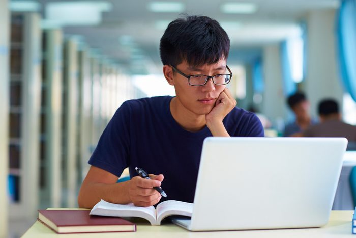 college student studying in the library with laptop