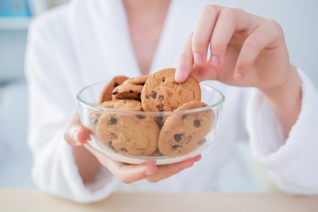 Woman at home grabs a chocolate chip cookie from a bowl.