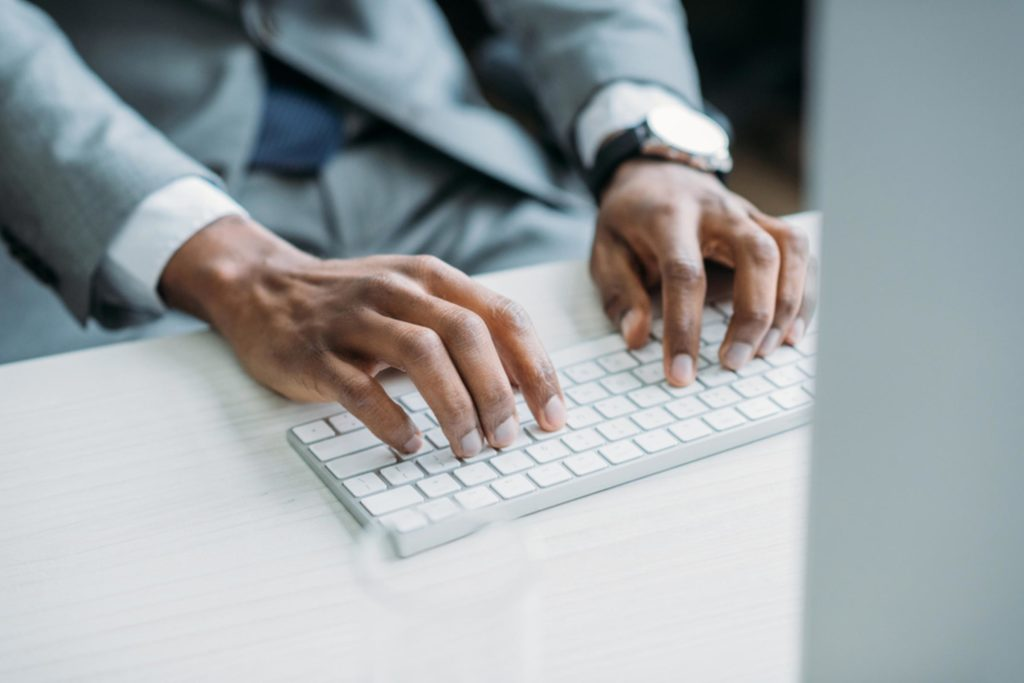 man's hands on computer keyboard