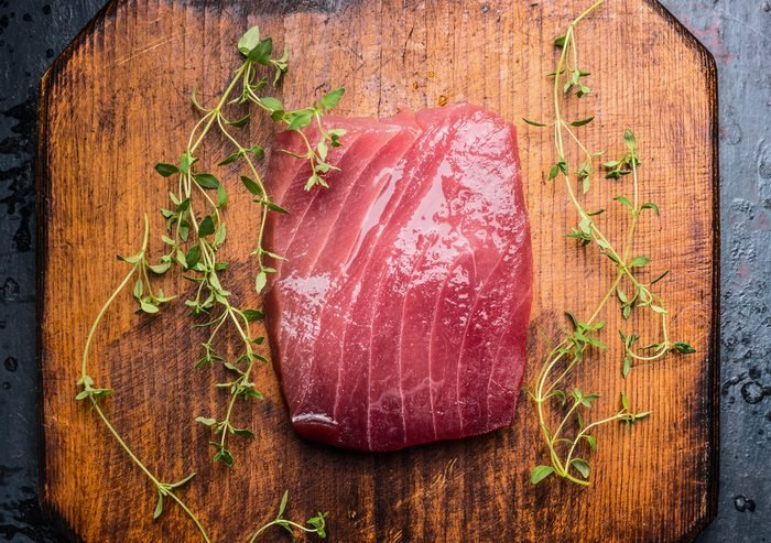 Tuna steak on rustic wooden background with fresh herbs, top view, close up. Seafood concept
