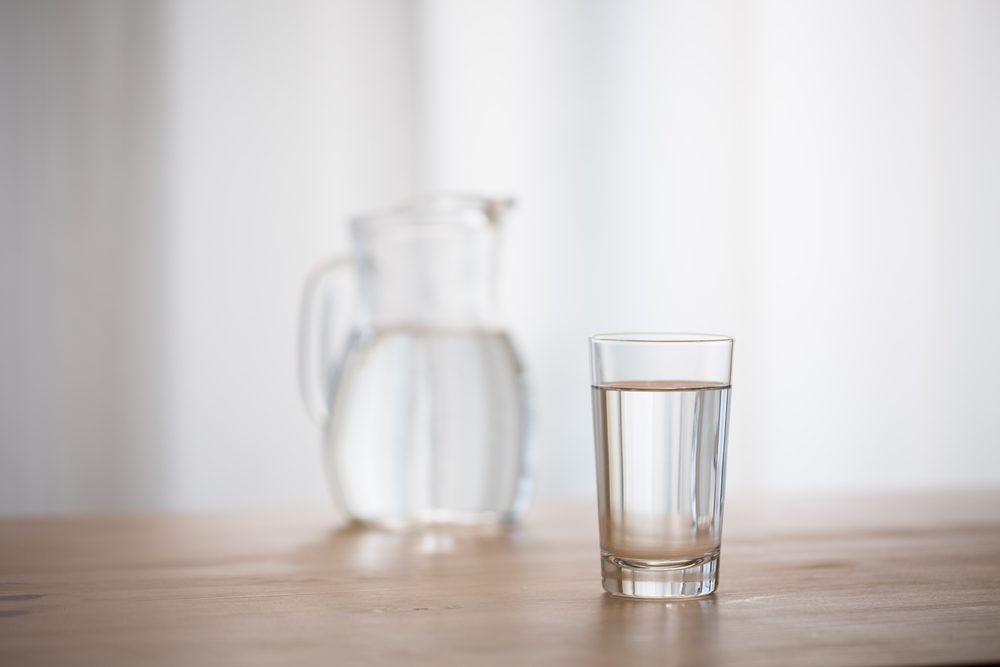 Glass of water and a pitcher of water in the background