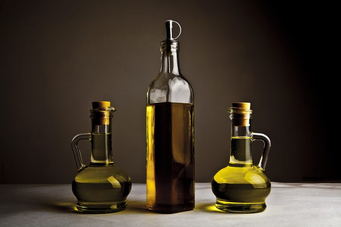 Backdrop of three olive oil glass transparent bottle with cork stand on white table on kitchen space room, on dark black background Empty space for inscription