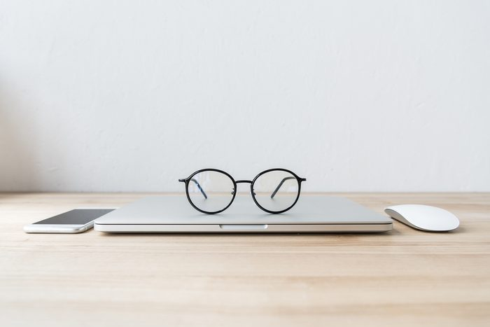 folded laptop at workplace with eyeglasses, smartphone and mouse