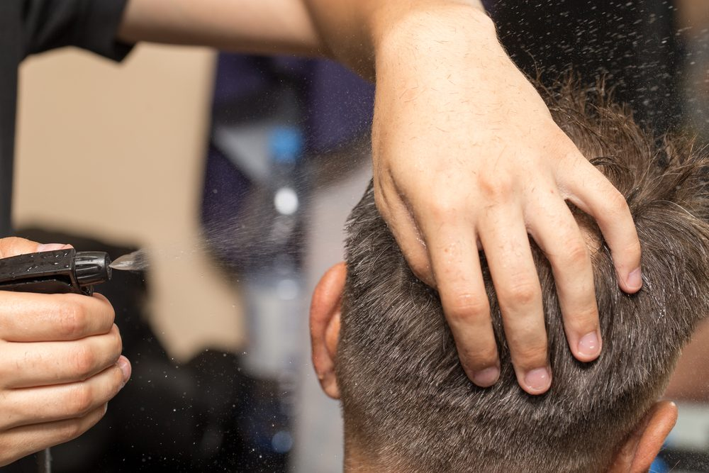 spraying with hair spray in beauty salon