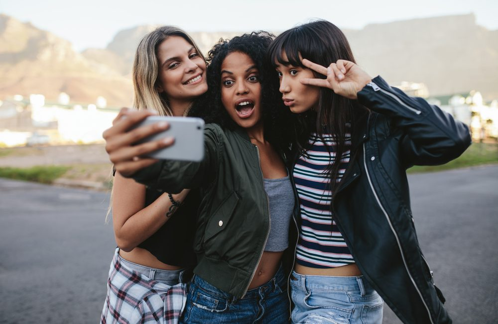 Happy female friends making selfie with smart phone. Multi ethnic group of women hanging out in the city and taking self portrait with mobile phone.