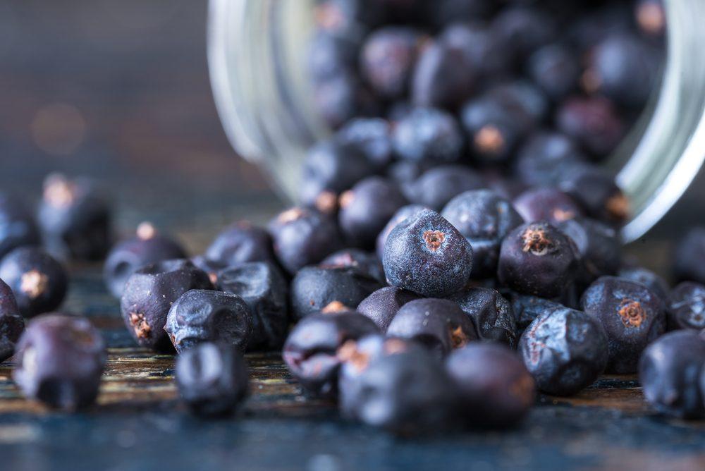 Juniper berries spilled from a glass spice jar